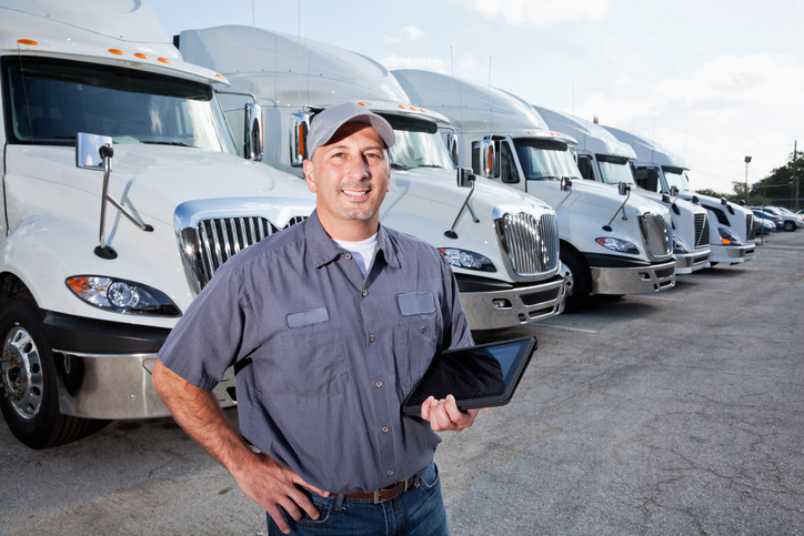 man standing in front of truck fleet holding an iPad
