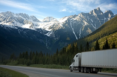 image of big rig driving through mountains
